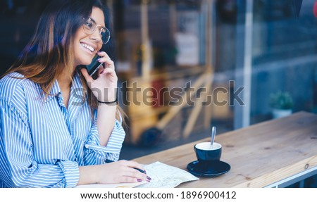 Happy young brunette female with toothy smile having glass of milk with cookie Stock photo © pressmaster