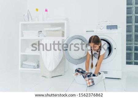 Pretty little girl householder poses inside of washing machine, takes checkered shirt from basin, en Stock photo © vkstudio