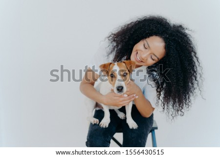 Glad dark skinned girl plays with jack russell terrier dog, have fun together, poses against white b Stock photo © vkstudio