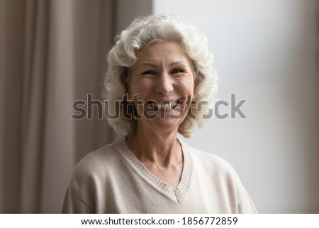 Photo of pleasant looking curly haired lady with toothy smile, dressed formally, poses indoor, holds Stock photo © vkstudio