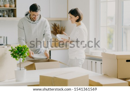 Photo of glad married woman and man unpack dinnerware from boxes, dressed casually, hold plates, pos Stock photo © vkstudio