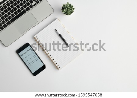 Notebook with pen, monthly planner in the phone, plant in flowerpot and laptop Stock photo © pressmaster
