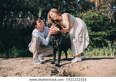 Young affectionate smiling woman embracing black retriever sitting on snow Stock photo © pressmaster