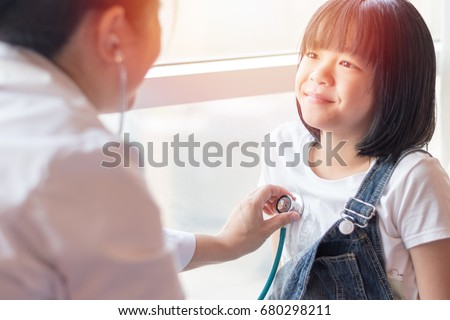 Caring female pediatrician listens childs lungs or heart with phonendoscope. Little girl comes on ex Stock photo © vkstudio