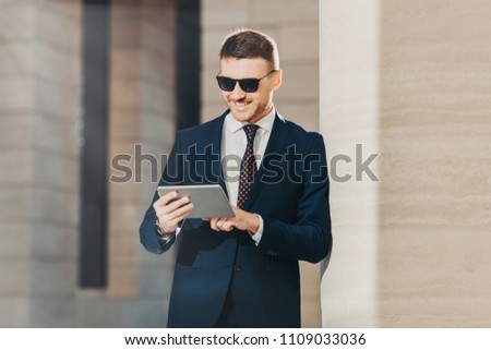 Fashionable young male banker examines future banking agreement, uses modern touch pad, reads import Stock photo © vkstudio