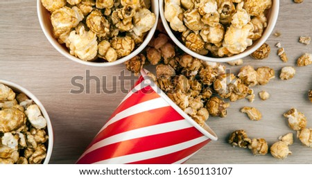 red cardboard cup with sprinkled sugar popcorn on a wooden table Stock photo © mizar_21984