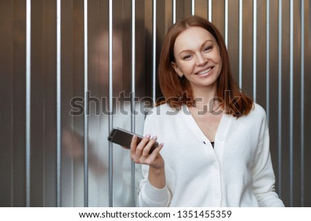 Satisfied female entrepeneur with toothy smile, wears white jumper, holds modern cell phone, sends t Stock photo © vkstudio