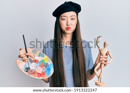 Image of young beautiful asian girl wearing beret blowing air ki Stock photo © deandrobot