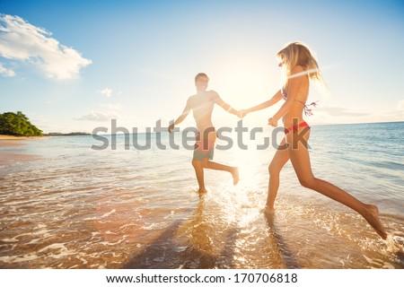 Happy newlyweds couple running on the beach holding hands, honeymoon travel. Asian caucasian multira Stock photo © Maridav