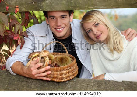 young couple behind a wooden barrier in autumn, the man is holding a wickerwork basket containing mu Stock photo © photography33