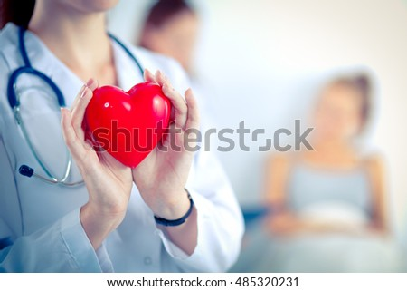 female doctor with stethoscope holding red human heart at hospit stock photo © hasloo