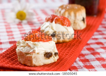 Scone halves with strawberries, clotted cream and a jar of raspb Stock photo © raphotos