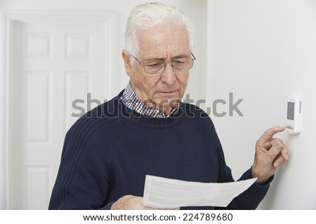 Stock photo: Worried Senior Man With Bill Turning Down Central Heating Thermo