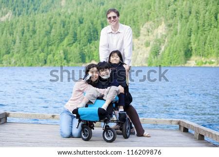 Interracial family surrounding disabled boy in wheelchair outdoo Stock photo © jarenwicklund