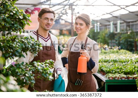 Happy gardeners holding watering can and pulveriser for spraying flowers  Stock photo © deandrobot