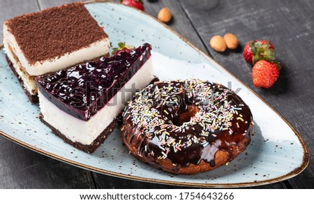 Hand picking donut with sweet strawberry topping from a plate Stock photo © stevanovicigor