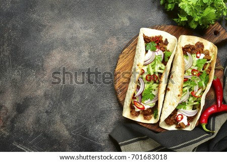 mexican tortilla with meat beef and stewed vegetables and spicy sauce with on a newspaper stock photo © mcherevan