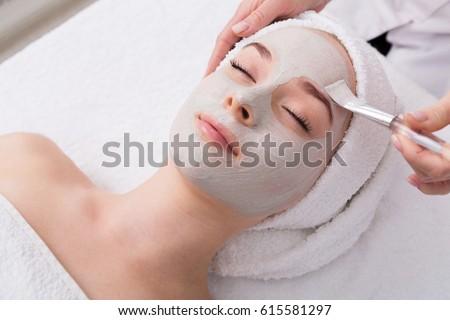 Spa treatment. Beautiful woman with facial mask at beauty salon. Stock photo © Yatsenko
