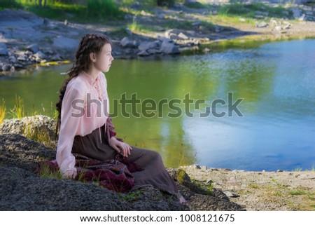 Gyönyörű fiatal nő ül kő part napos Stock fotó © Massonforstock
