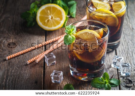 Cuba Libre cocktail with cola, lime and ice in glass, cold longdrink Stock photo © yelenayemchuk