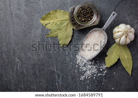 Dark culinary background with bay leaves, salt, pepper and garlic, view from above, copy space for r Stock photo © yelenayemchuk
