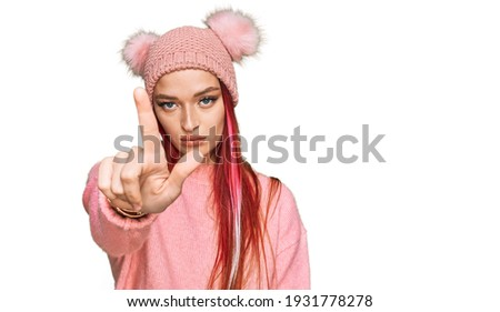 close up portrait of upset woman in winter clothes showing thumb stock photo © deandrobot