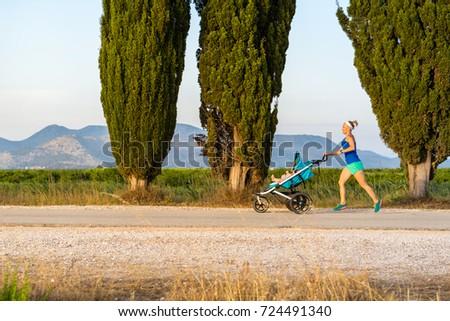Running mother with stroller enjoying motherhood at sunset lands Stock photo © blasbike