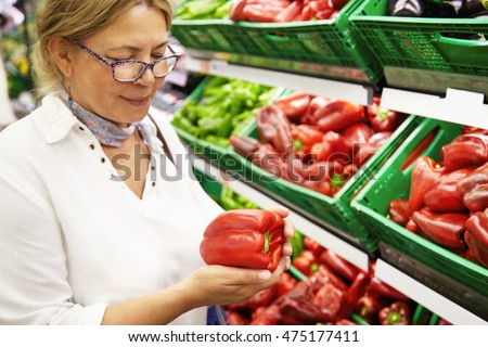 Stockfoto: Good Looking Senior Woman Wearing Glasses Buys Pepper On Market