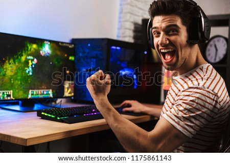 portrait of ecstatic gamer guy in headphones screaming and rejoi stock photo © deandrobot