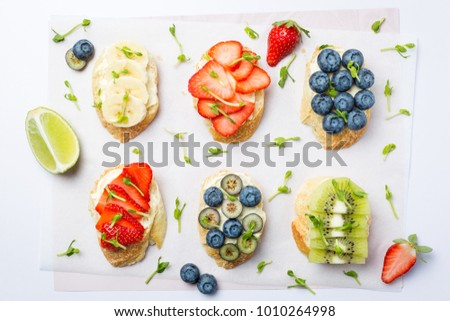 Fresh healthy mini sandwiches with cream cheese, fruits and berries. Strawberries, blueberries, bana Stock photo © DenisMArt