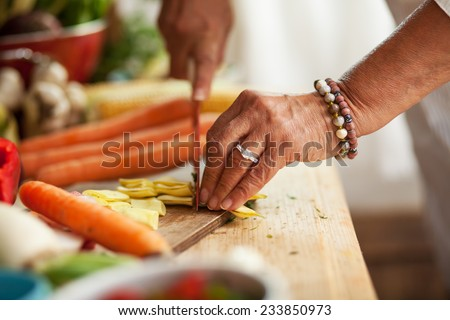 Fresh leek slices cut into the hands of a female cook on a wooden board on the kitchen table around  Stock photo © artjazz