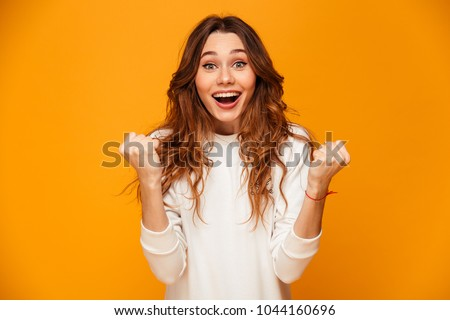 Portrait of happy woman 20s with long hair rejoicing and holding Stock photo © deandrobot