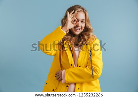 Image of happy woman 20s wearing yellow raincoat laughing while  Stock photo © deandrobot