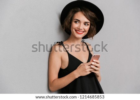 photo of adorable woman 20s wearing black dress and hat speaking stock photo © deandrobot