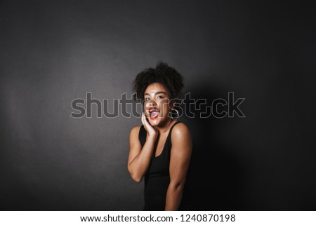 Portrait of joyous afro american woman wearing black dress stand Stock photo © deandrobot