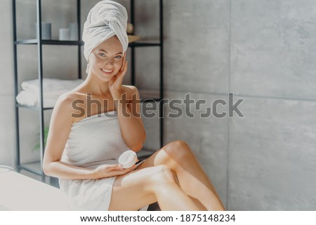 Photo of smiling woman wrapped in towel applying cream at face,  Stock photo © deandrobot