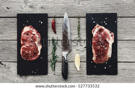 Raw sirloin beef steak on old chopping board with salt and pepper and vintage meat hatchets and hamm Stock photo © DenisMArt