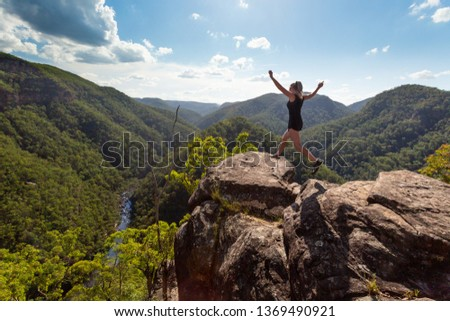Girl leaping on high rocky cliff with mountain river backdrop Сток-фото © lovleah