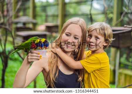 Mom and son feed the parrot in the park. Spending time with kids concept BANNER, LONG FORMAT Stock photo © galitskaya