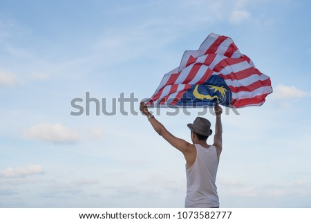 young man travels in malaysia holds the malaysian flag banner long format stock photo © galitskaya
