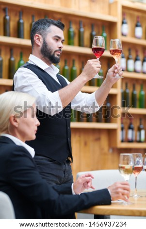 One of contemporary sommeliers comparing colors of wine in two glasses Stock photo © pressmaster
