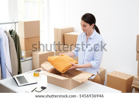 Young female online shop manager putting folded velvet yellow trousers into box Stock photo © pressmaster