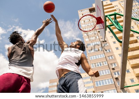 Young active players in sportswear jumping while trying to catch the ball Stock photo © pressmaster