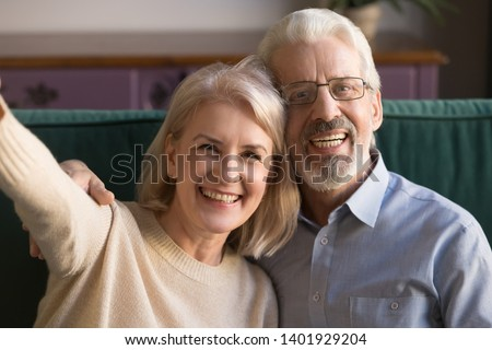 Happy mature active spouses looking at smartphone camera while making selfie Stock photo © pressmaster