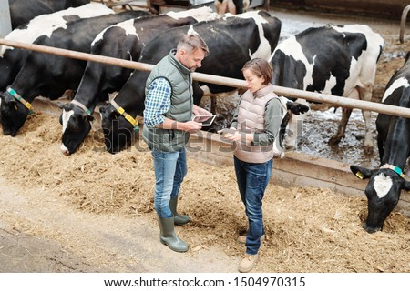 contemporary scientists or workers of farm discussing characteristics of hay stock photo © pressmaster