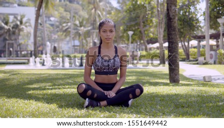 Asian sportive woman sitting with crossed legs and stretching arms in park Stock photo © dash