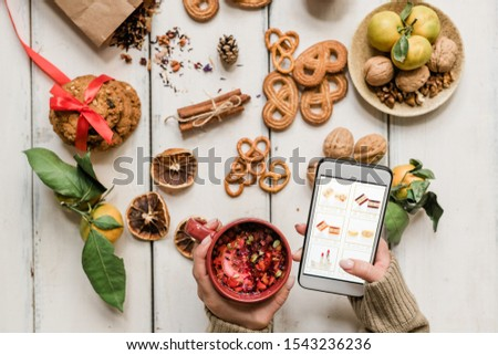 Girl holding drink and smartphone while scrolling through goods in online shop Stock photo © pressmaster