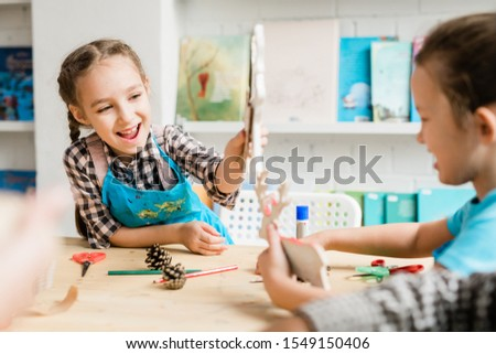 Naughty schoolgirls having fun at lesson and playing with self-made toys Stock photo © pressmaster