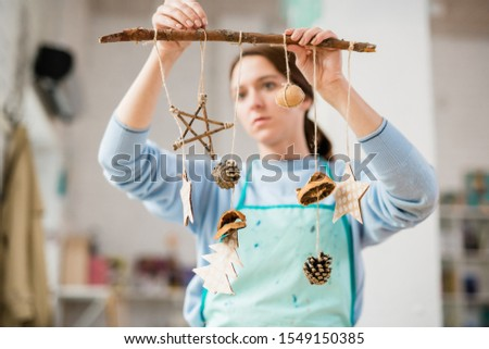 Young woman holding stick with handmade carton Christmas decorations Stock photo © pressmaster