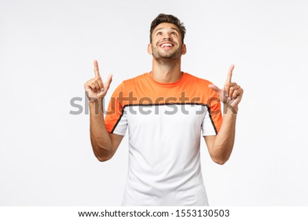 Amazed, pleased good-looking bearded man in sports t-shirt, raise head and pointing up astonished, s Stock photo © benzoix